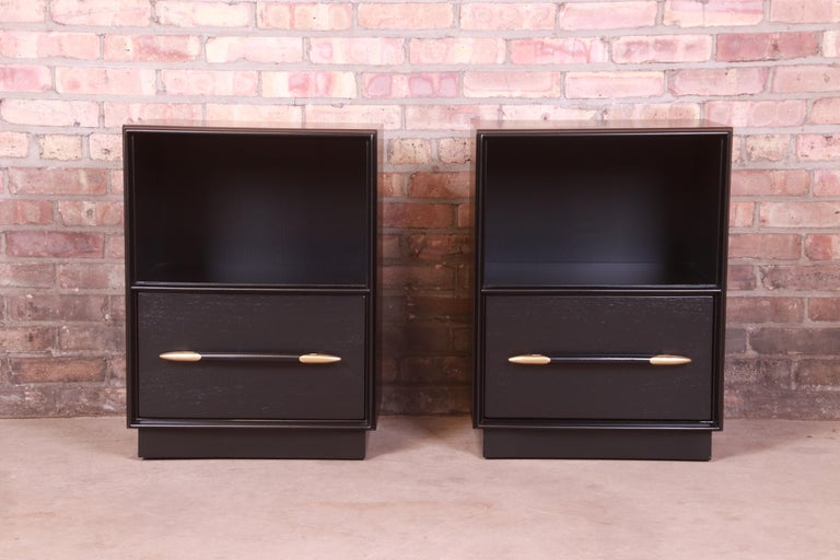 A gorgeous pair of Mid-Century Modern nightstands  By T.H. Robsjohn-Gibbings for Widdicomb  USA, 1950s  Black lacquered walnut, with unique brass and lacquered spear-shaped drawer pulls.  Measures: 19