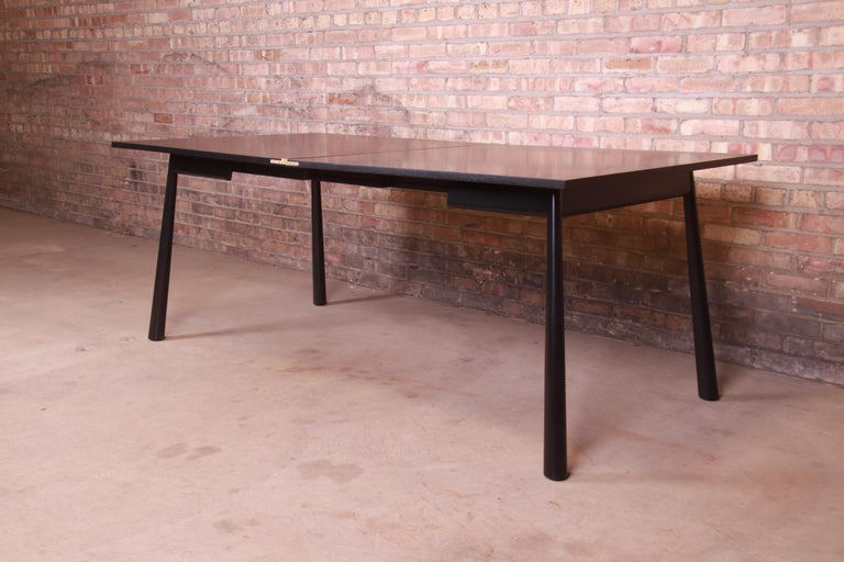 An exceptional Mid-Century Modern flip top dining table or game table  By T.H. Robsjohn-Gibbings for Widdicomb  USA, 1950s  Black lacquered walnut, with original brass hardware.  Measures: 38