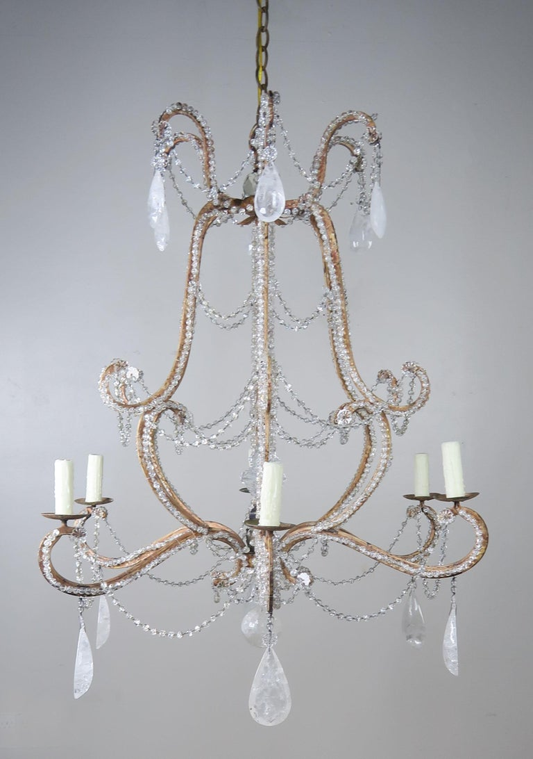 Rococo Louis XV style six-light painted wrought iron chandelier adorned with almond shape rock crystals and garlands of faceted beads throughout. Center crystal finial. The fixture is newly rewired with drip wax candle covers and includes chain and