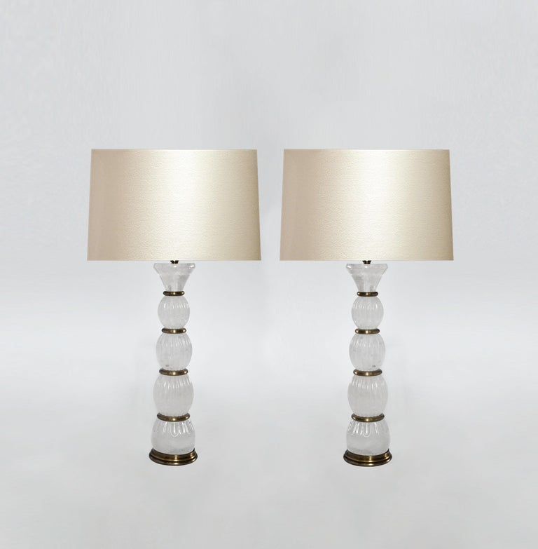 Pair of rock crystal lamps with antique brass insert decoration. Created by Pheonix Gallery, NYC. To the top of the rock crystal is 17 in. (Lampshade not included). Custom size and metal finish upon request.