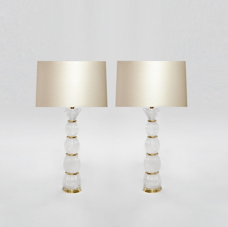 Pair of rock crystal lamps with polish brass insert decoration. Created by Pheonix Gallery, NYC. To the top of the rock crystal is 17 in. (Lampshade not included). Custom size and metal finish upon request.