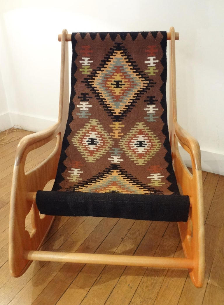 Apostolos Porsanidis, France. Large wood rocking armchair, 2009 With teck and exotic wood sculpted open sides and Kilim wool tapestry seating. Measures: Height 35.5 x width 27.5 x depth 42 inches. With its original small scale model. Apostolos
