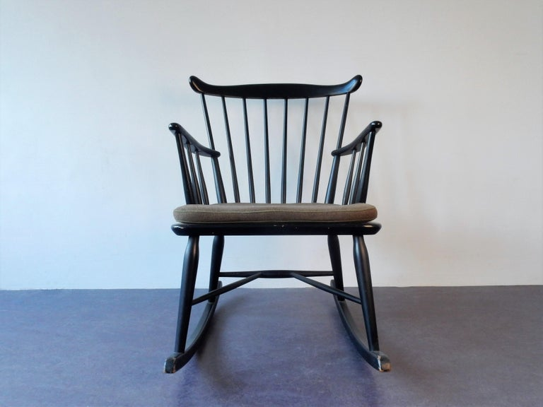 This is a very nice black lacquered spindle back rocking chair from Farstrup Mobler, Denmark. It comes with a cushion that does show signs of age and use and this could be replaced for a newly upholstered cushion. This chair is in a very good