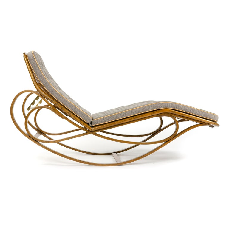 An adjustable rocking chaise with caned seat and back with bent ash frame and a cushion upholstered in grey savak with natural leather welting.