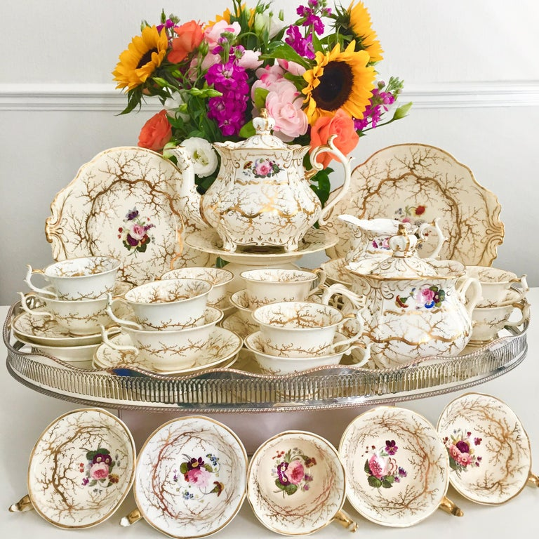 This is a stunning full tea service made by Rockingham in circa 1832, which was the Rococo Revival era. It is cream white with gilt and beautiful hand painted flowers. The service consists of a large teapot with stand, 10 teacups, 7 coffee cups, 12