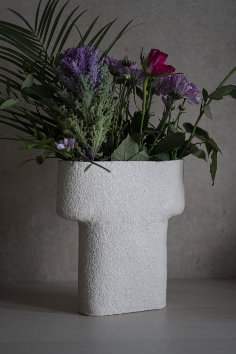 Pillar-vase takes inspiration from the ancient human-made rock formations. It references the ancient architecture and the human touch in carved stones. The sculptural vase displays flowers in a horizontal fan-like alignment and the electric blue