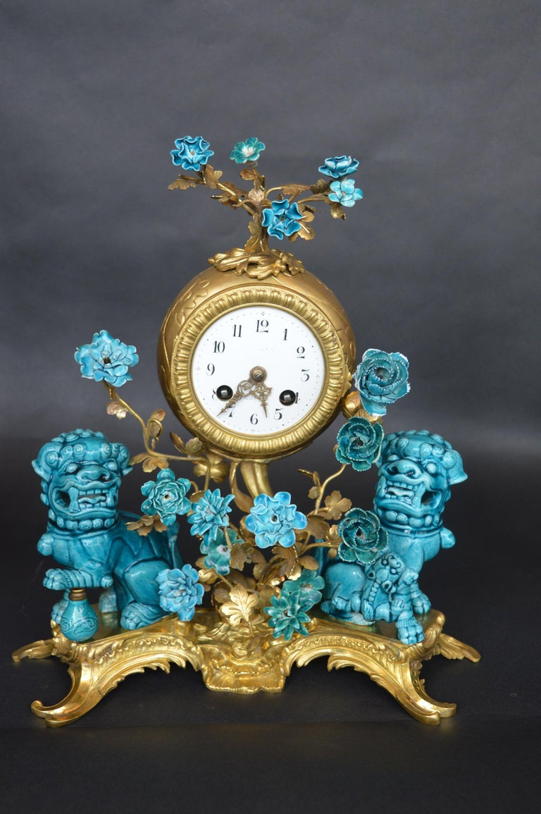 A French Rococo chinoiserie style three-piece gilt bronze and porcelain clock garniture, circa 1900, comprising a gilt bronze mantel (fireplace) clock surmounted with turquoise glazed floral blossoms on gilt bronze wire stems over a cylindrical