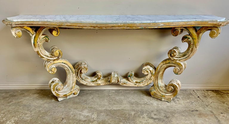 Rococo style painted and parcel gilt console with inset Carrara marble top. Beautiful scrolled swirling acanthus leaves make up this elegant piece. We actually have a pair of these if needed.