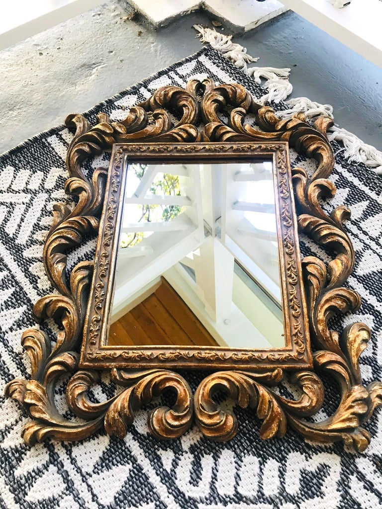 Hollywood Regency Baroque style mirror features a solid wood frame with hand carved designs and antique gold leaf finish. The ornamental frame features stylized scrolls of foliage and Prince of Wales plumes. The rectangular inner frame has a series