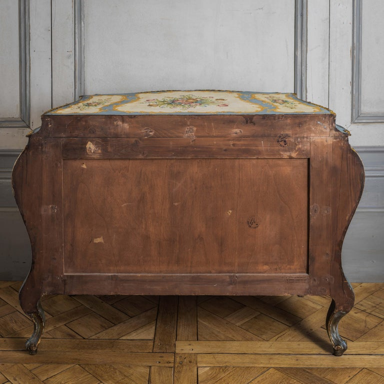 A vivacious Rococo style Venetian bombe chest from the early 1900's, hand painted with delicate floral motifs on the main colours of old white and cobalt blue with gilded highlights.