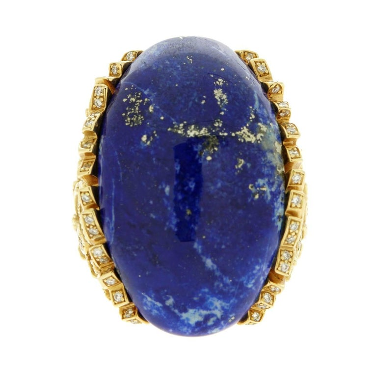 "A magnificent custom piece by Rodney Rayner featuring a Lapis Lazuli central stone measuring 1.25"" in length by .75"" adorned with round brilliant cut diamonds set in 18k yellow gold.  Size: 6 1/2"