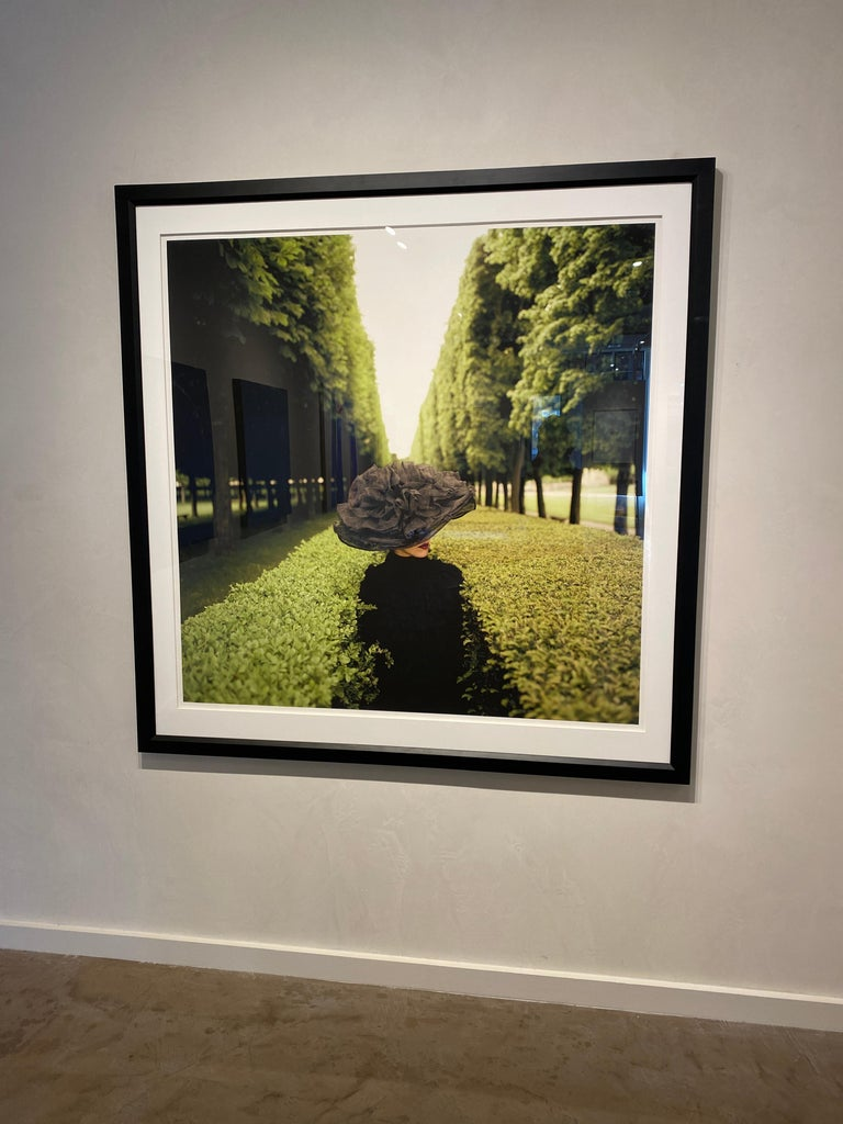 Color photograph of a woman in a wonderfully large and sculptural hat between lush green hedges in Paris. Image size: 50 x 50 inches  Framed size: 60 x 60 inches Each image is part of an edition of 25. Price increases as the edition sells out. His