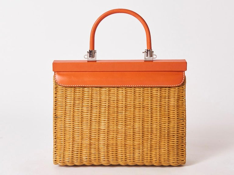 Rodo, made in Italy, rattan and orange tone leather handbag. Upper part of the bag is leather including the top handle . The closure is magnetic. Body of the bag is rattan. Interior is lined in khaki canvas with a zippered compartment.