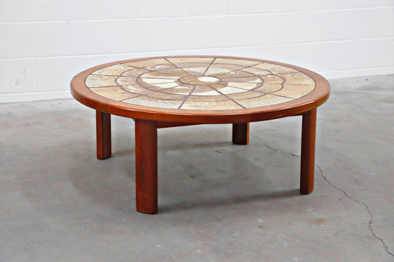 A classy and stylish Tue Poulsen and Roger Capron style Mid-Century Modern teak and ceramic tile coffee table featuring ceramic art tiles inset into a round teak top atop for teak legs. The ceramic tiles are placed in a circular pattern with a cloud