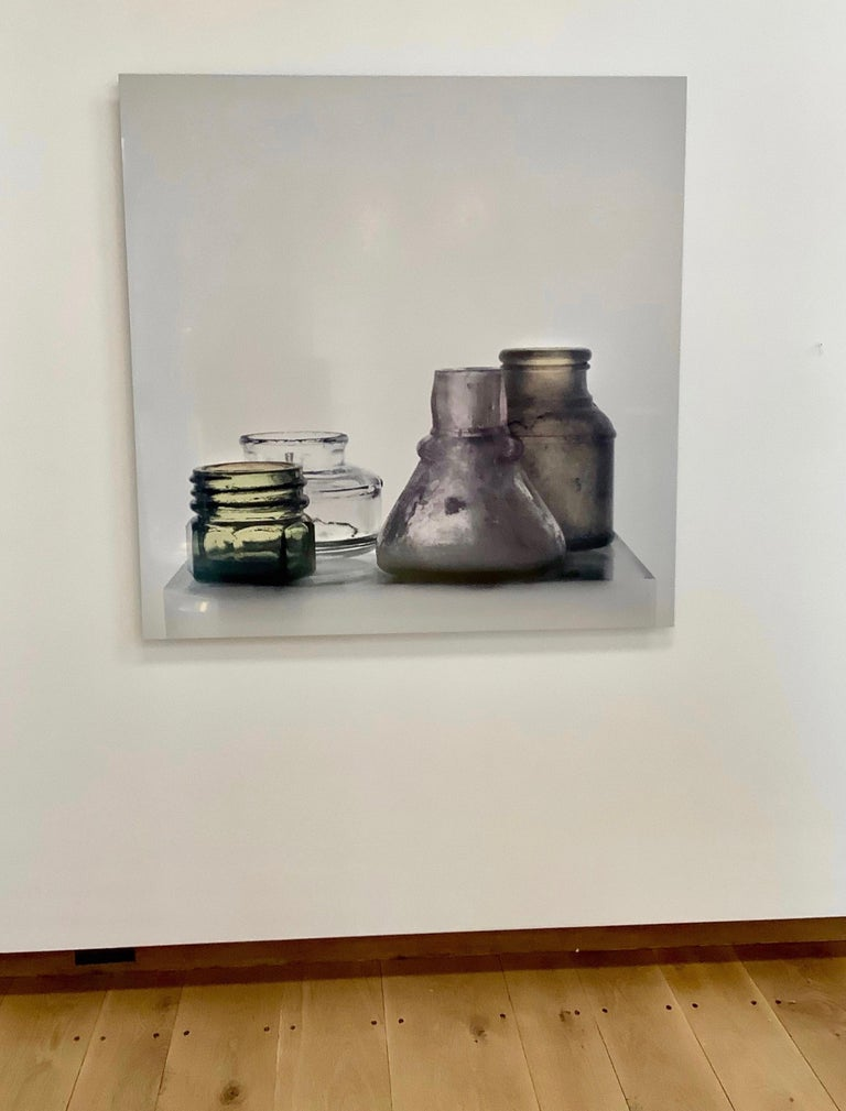 In this square still life photograph printed as a dye transfer on aluminum, an arrangement of glass jars, one clear and some in faintly tinted shades of frosted gray and light green, stand at varying heights atop a nearly transparent glass cube