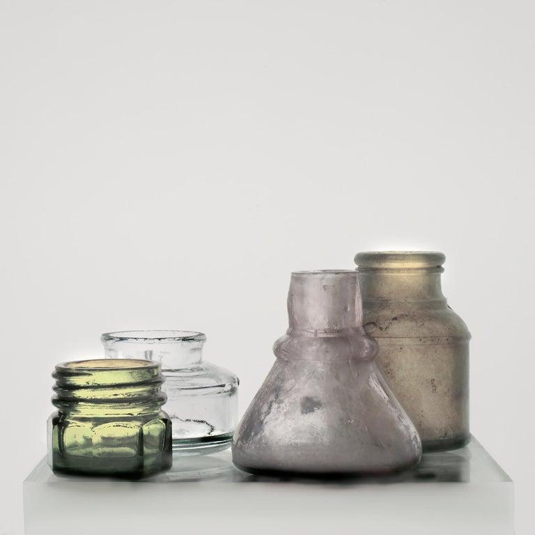 Roger Ricco Still-Life Photograph - Small Bottles 17, Square Still Life Photograph of Glass Bottles on White