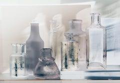 Small Bottles 24a Invert, Still Life Photograph of Glass Bottles in White, Gray
