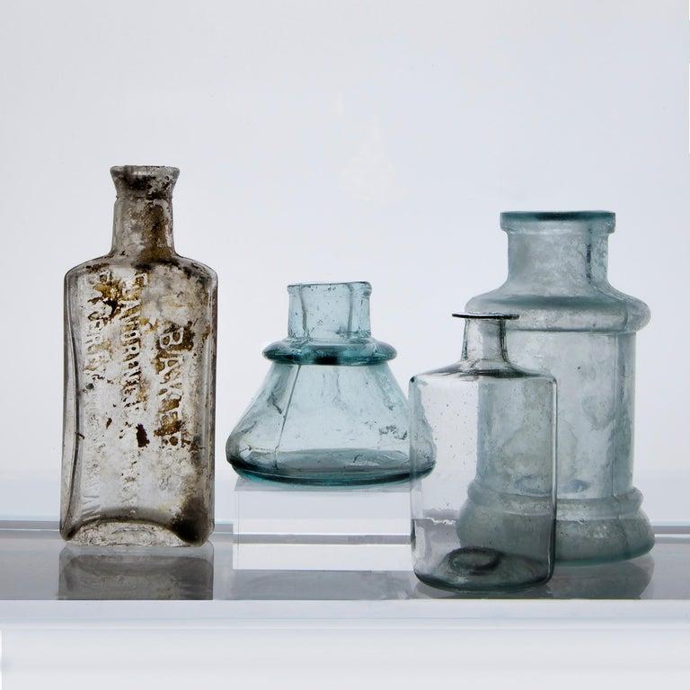 Roger Ricco Still-Life Photograph - Small Bottles Nine, Square Still Life Photograph of Glass Bottles on White