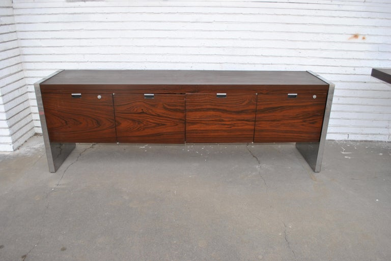 Roger Sprunger for Dunbar rosewood and chrome executive Credenza, 1970s.  A Mid-Century Modern rosewood and chrome credenza with generous storage and shelving. Six drawers and two file cabinets. Rich rosewood case with polished chrome