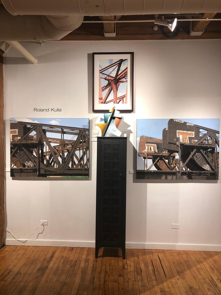 This painting captures a red iron girder beam steel bridge with bright blue skies in and urban architectural setting.  This acrylic painting on paper is framed in dark wood with a cream colored mat.  Rolland has always been fascinated by the built