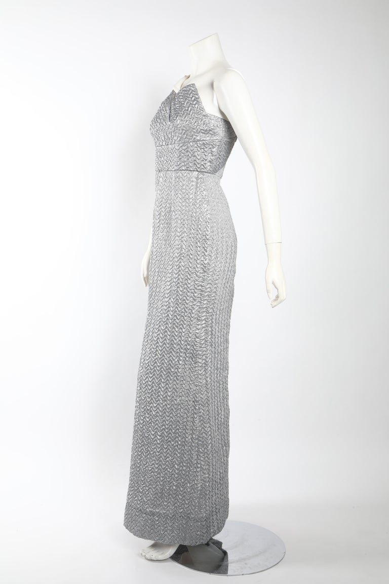 Floor-length column gown by Roland Mouret in silvery grey accented complimented by a white, structural neckline. This one-shouldered beauty is made of a textured fabric with a quilted effect and finished with a flare skirt and fitted waist. Size 4