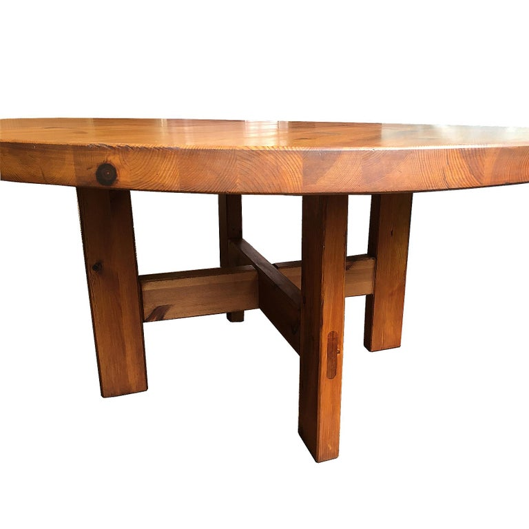 """The round top made of solid pine, on four rectangular feet joined by an X-shaped stretcher. With labels underneath """"Design Roland Wilhelmsson, Stockholm, Sweden"""" and """"Manufactured by AB Karl Andersson & Soner, Huskvarna, Sweden"""". Produced by Karl"""