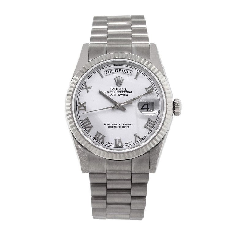 Brand: Rolex MPN: 118239 Model: Day Date Case Material: 18k White Gold Case Diameter: 36mm Crystal: Scratch resistant sapphire Bezel: 18k White Gold Fluted Bezel Dial: White dial with silver roman numerals. Date window at the 3 o'clock position. Day