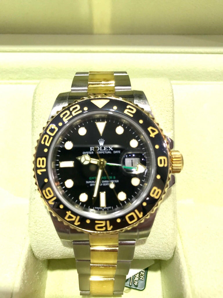 An excellent condition iconic Rolex GMT Master II with a ceramic bezel.  The watch features the Oyster bracelet, made up of solid 18 karat yellow gold and stainless steel links.  This watch has the original box and papers, including the warranty