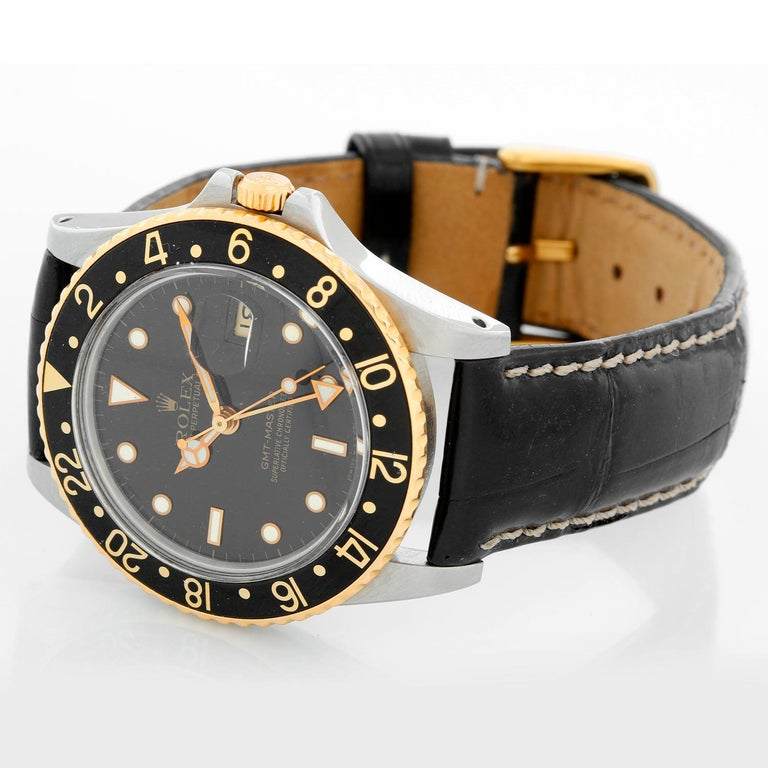Rolex 2-Tone GMT-Master 16753 on a Strap - Automatic winding. Stainless steel with gold bezel ( 40 mm ). Black dial with gold framed hour markers with date. Black alligator strap with tang buckle. Pre-owned with Rolex box and books
