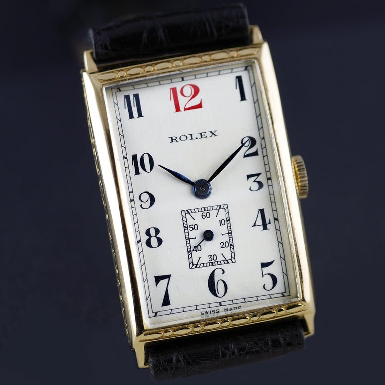 An Art Deco vintage wristwatch by Rolex dated 1927. This unusual and rare rectangular shaped Rolex wristwatch, with a distinctive red 12 and hand chased (engraved) case detailing, was made in the height of the Art Deco era. This is a very high grade