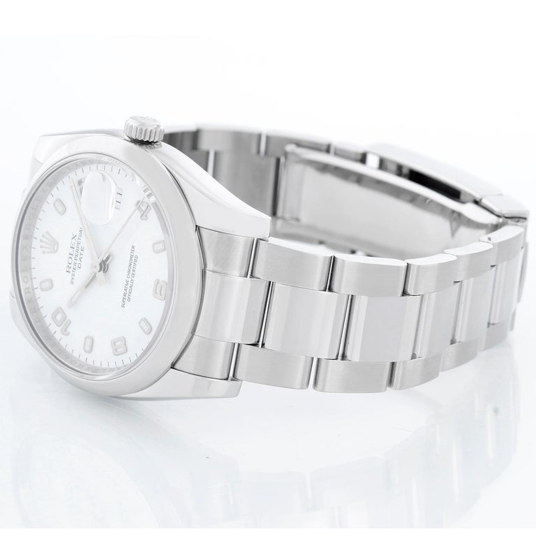 Rolex Date Oyster Perpetual Men's Watch 115200 - 115200. Stainless Steel ( 34 mm ) Smooth bezel. White dial with luminous hour markers. Oyster bracelet with deployant buckle. Pre-owned with Rolex box and book