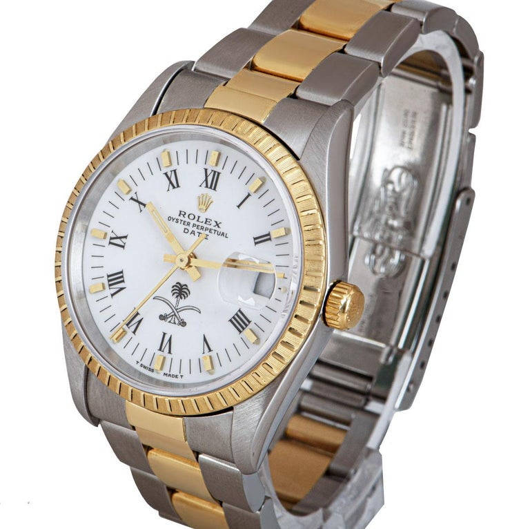 A 34 mm Stainless Steel and 18k Yellow Gold Oyster Perpetual Date Gents Wristwatch, white dial with roman numerals and applied hour markers, date at 3 0'clock, rare emblem of Saudi Arabia at 6 0'clock, a fixed 18k yellow gold engine turned bezel, a