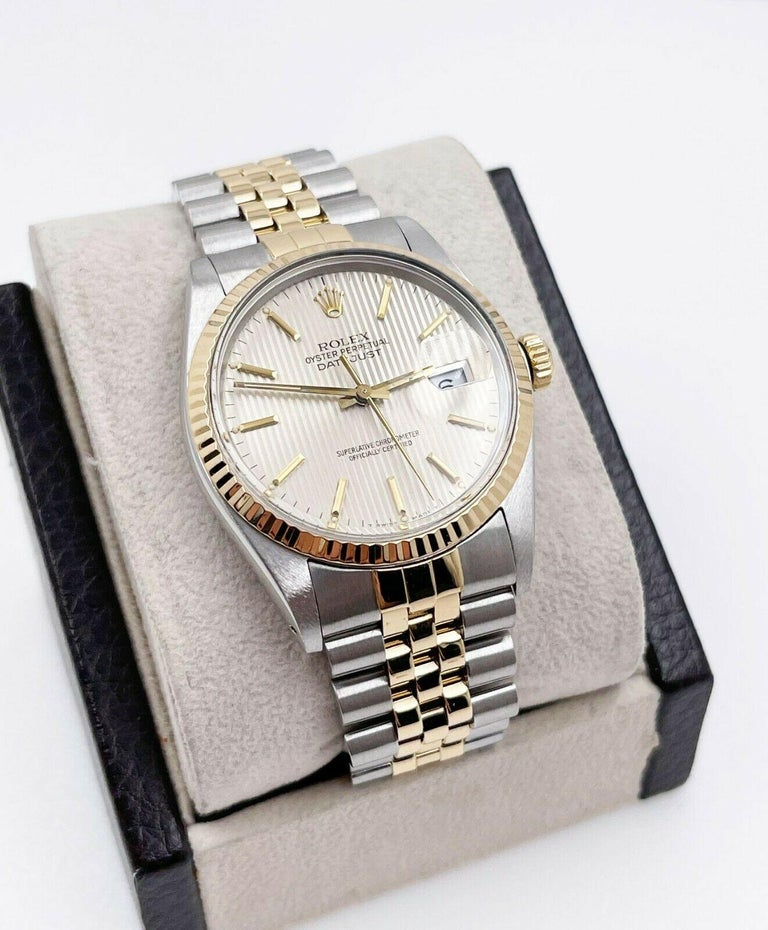Style Number: 16013     Serial: 911***     Model: Datejust      Case Material: Stainless Steel     Band: 18K Yellow Gold & Stainless Steel     Bezel:  18K Yellow Gold     Dial: Silver Tapestry Dial      Face: Acrylic      Case Size: 36mm