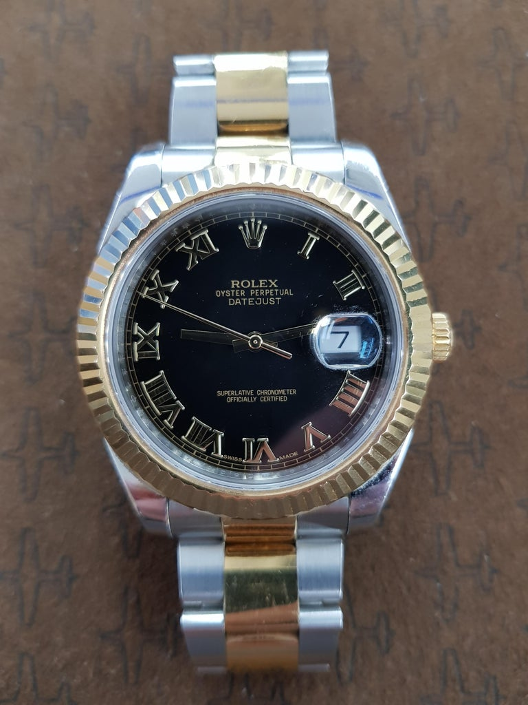 Rolex Date Just 2 in bi-metal stainless steel and yellow gold with a black dial and 41 mm fluted bezel. This watch comes with full Rolex certification.