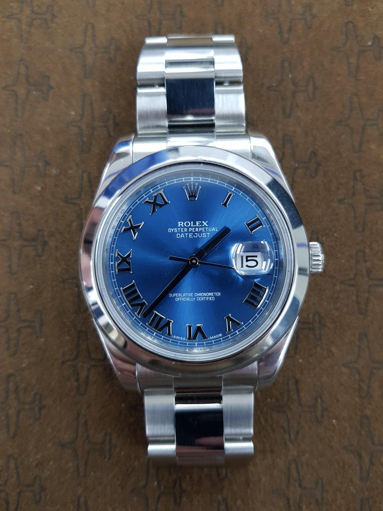 Rolex Date Just 2 in stainless steel with a 41 mm blue dial. This watch comes with full Rolex certification.