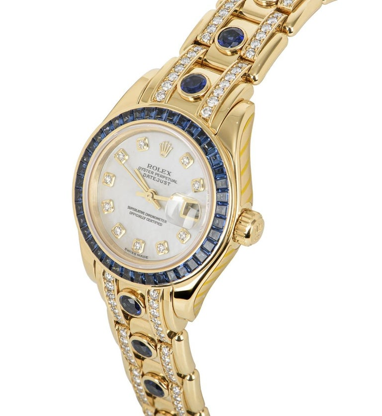 A Yellow Gold 29mm Datejust Pearlmaster by Rolex. Features a mother of pearl dial set with 10 round brilliant cut diamond hour markers and 40 baguettecut sapphires set on the bezel. Fitted with a Pearlmaster bracelet set with 13 rub-over set