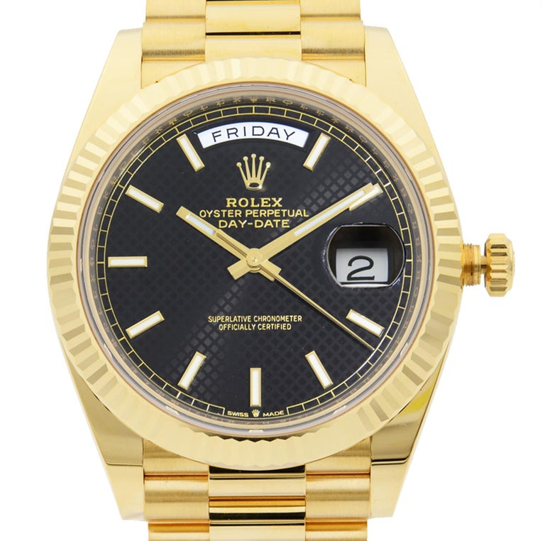 This  never been worn  Rolex Day-Date 228238 is a beautiful men's timepiece that is powered by mechanical (automatic) movement which is cased in a yellow gold case. It has a round shape face, day & date dial and has hand sticks style markers. It is