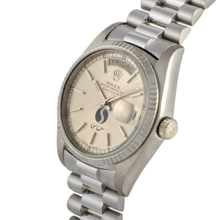 The Rolex Day-Date SNAS Aviation watch, reference number 18039, boasts a 36 mm 18K white gold case fitted with a fluted 18K white gold bezel. The case is mounted onto an 18K white gold President bracelet. The silver dial boasts the logo of the Saudi