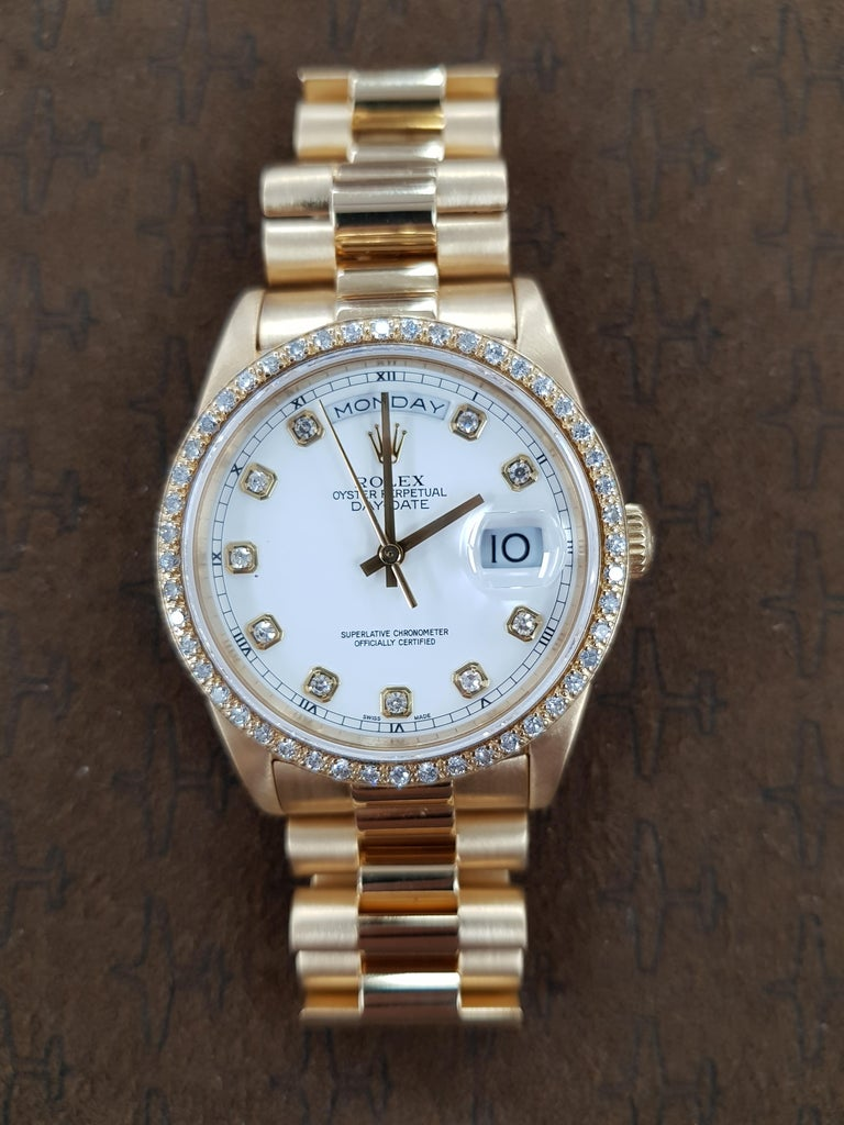 Rolex Day Date in yellow gold with a unique diamond bezel and 36mm dial.