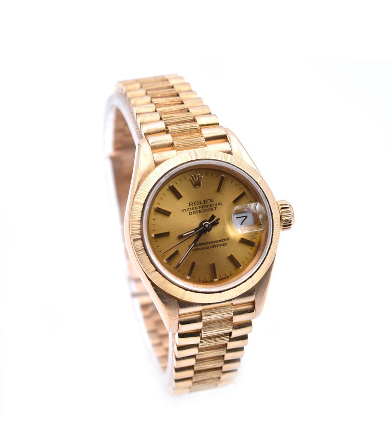 Movement: automatic  Function: hours, minutes, seconds, date Case: round 26mm 18k yellow gold case with engine turned bezel, sapphire protective crystal, screw-down crown, water resistant to 30 meters  Band: 18k yellow gold bark presidential
