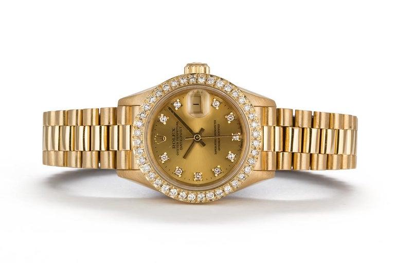 We are pleased to offer this 1991 Rolex 18k Yellow Gold & Diamond Ladies Datejust President 69178. This classic ladies watch features a solid 18k Yellow gold design with high quality custom diamond bezel and diamond dial. It will fit up to a 6.5