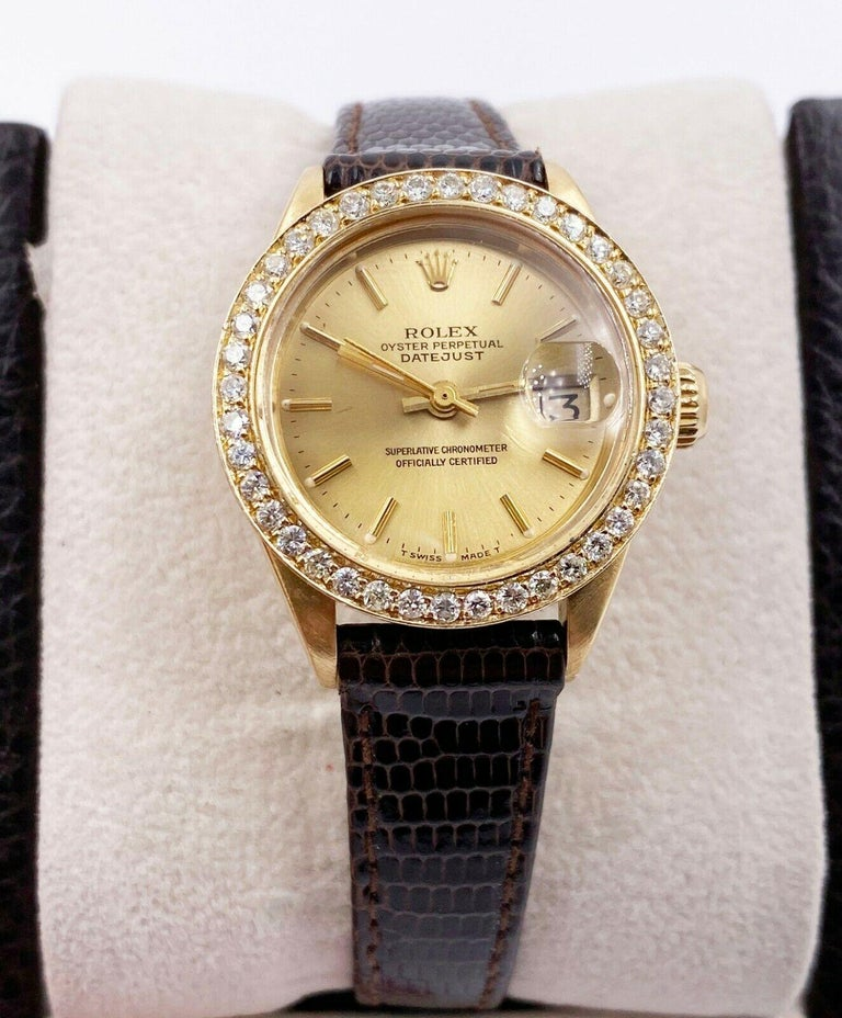 Style Number: 6917     Serial: 3436***    Model: Ladies President Datejust     Case Material: 18K Yellow Gold     Band: Brown Leather Band - Custom Clasp     Bezel:  Custom Diamond Bezel     Dial: Champagne     Face: Acrylic     Case Size: 26mm