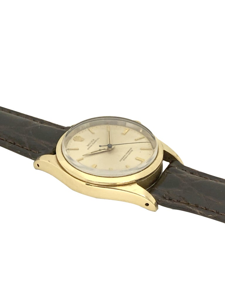 Circa 1980 Rolex Oyster Perpetual Reference 1014 Wrist Watch, 34 M.M. Yellow Gold Shell case with Stainless Steel Oyster back, Caliber 1130 Automatic Self Winding Movement. Silver Satin Dial with Raised Baton Markers and a sweep seconds Hand,