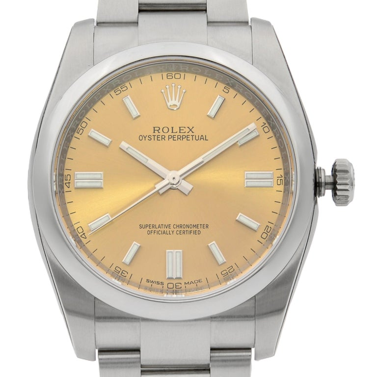 This display model Rolex Oyster Perpetual 116000 is a beautiful men's timepiece that is powered by mechanical (automatic) movement which is cased in a stainless steel case. It has a round shape face, no features dial and has hand sticks style