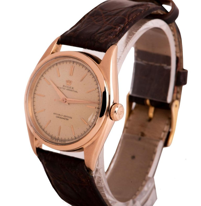 An 18k Rose Gold Oyster Perpetual Bubbleback Vintage Gents Wristwatch, original silver dial with applied hour markers, a fixed 18k rose gold bezel, a brown leather strap with a gold plated pin buckle (both not by Rolex), plastic glass, automatic
