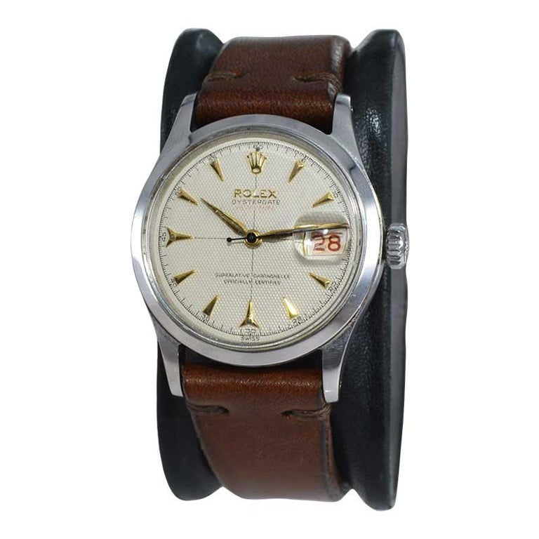 FACTORY / HOUSE: Rolex Watch Company STYLE / REFERENCE: Oyster Perpetual Date  METAL / MATERIAL: Stainless Steel CIRCA / YEAR: 1954 DIMENSIONS / SIZE: 42mm x 34mm MOVEMENT / CALIBER: Perpetual (Automatic) Winding / 22 Jewels / Cal.1060 DIAL / HANDS: