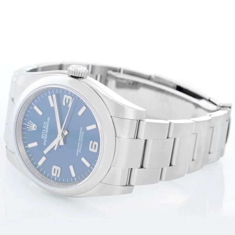 Rolex Oyster Perpetual Men's Stainless Steel Watch 116000 - Automatic winding, 31 jewels, sapphire crystal. Stainless steel case with smooth bezel (36mm diameter). Blue dial with luminous hour markers. Stainless steel Oyster bracelet. Pre-owned with