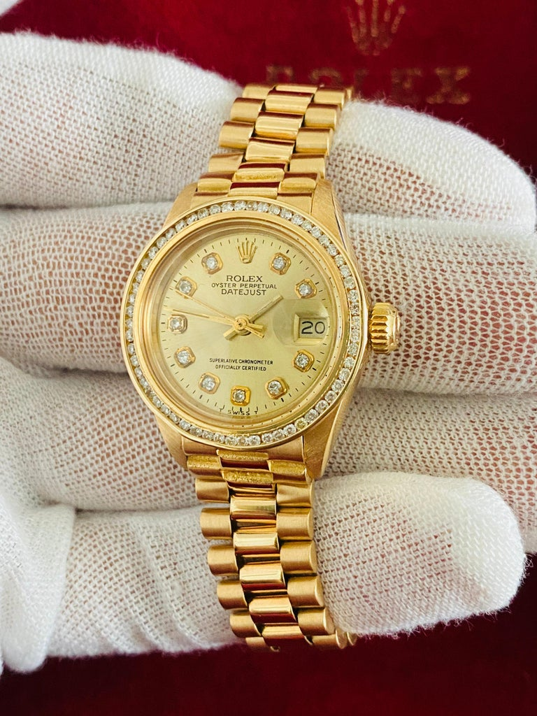 Brand: Rolex Model: Oyster Prepetual Datejust. 6917 Metal: 18K yellow gold  Diameter: 26mm  Movement: Automatic Custom diamond diamond and diamond bezel 1.20 carat diamonds total. SI clarity, G-H color. Bezel diamonds set in channel setting.  Comes