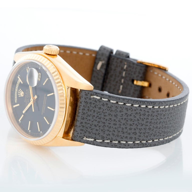 Rolex President Day-Date Men's 18k Gold Watch 18038 - Automatic winding; quick-set; sapphire crystal. 18k yellow gold case with fluted bezel . Black dial with stick hour markers. Grey leather strap with tang buckle . Pre-owned with Rolex box and