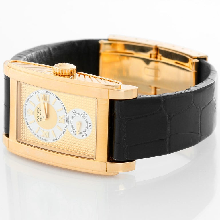 Rolex Prince Cellini Men's 18k Yellow Gold Watch 5440/8 - Manual winding. 18k yellow gold case with exposition back. Gold textured dial and round ivory colored hour/minutes dial with Roman numeral markers and seconds subdial below. Black strap band